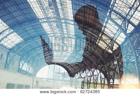 Double exposure of man with lap top on the train station