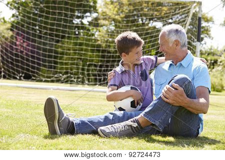 Grandfather And Grandson Playing Football In Garden