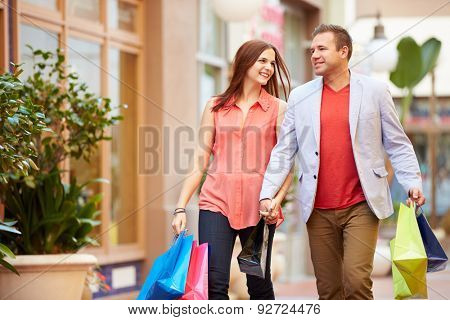 Young Couple Walking Through Mall With Shopping Bags