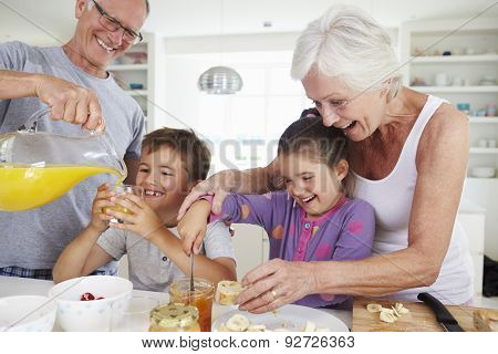 Grandparents With Grandchildren Making Breakfast In Kitchen