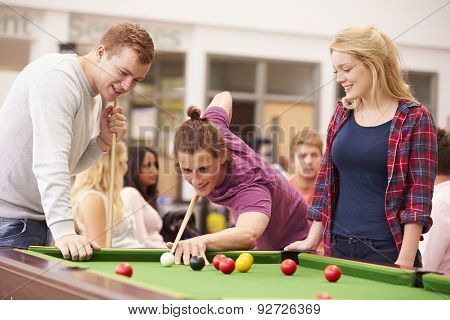 College Students Relaxing And Playing Pool Together