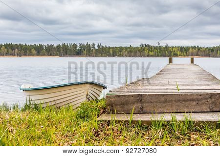 White Rowing Boat Next To Wooden Pier