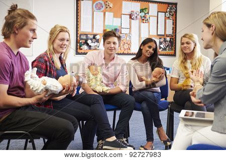 Teacher Helping Students Taking Childcare Course