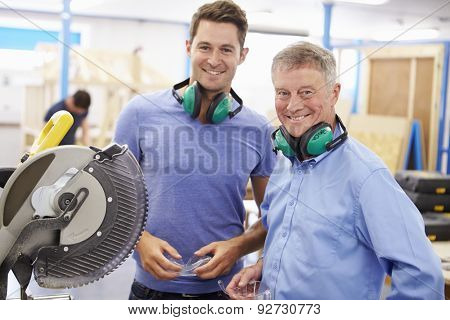 Student And Teacher In Carpentry Class With Circular Saw