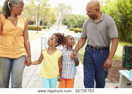 Grandparents Walking Grandchildren In Park
