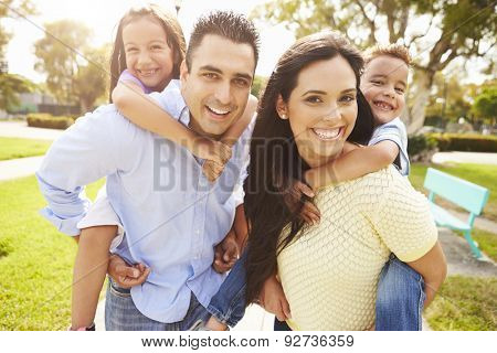 Parents Giving Children Piggyback Ride In Garden