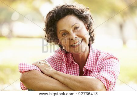 Portrait Of Senior Hispanic Woman Sitting In Park