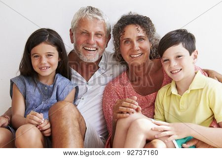 Portrait Of Grandparents With Grandchildren Sitting By Wall