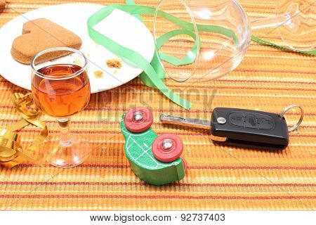 Car Key And Overturned Model Vehicle With Glass Of Wine