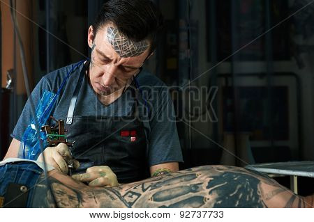 Tattoo Artist Drawing A Tattoo