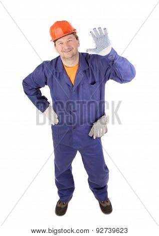 Working man smiling with hand raised.
