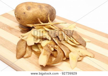 Whole Potato And Peels Lying On Wooden Cutting Board