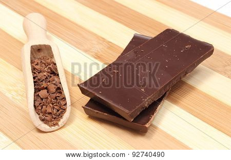 Stack Of Dark Chocolate And Grated On Wooden Spoon