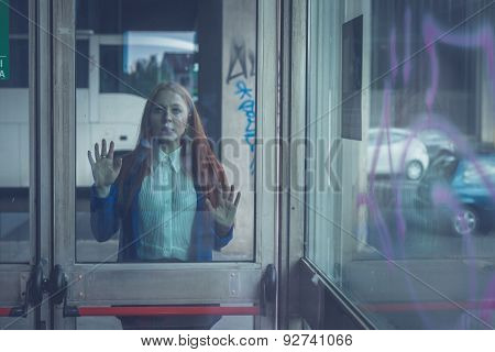 Beautiful Redhead Girl Posing Behind A Glass Door