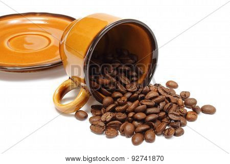 Overturned Cup And Heap Of Coffee Grains On White Background