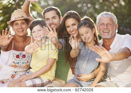 Multi Generation Family Sitting In Garden And Waving