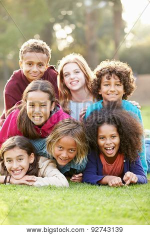Group Of Children Lying On Grass Together In Park