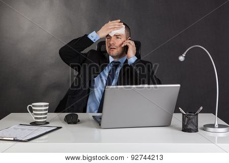 Businessman Holding Forehead In Office.