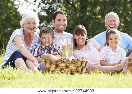 Multi Generation Family Enjoying Picnic In Countryside
