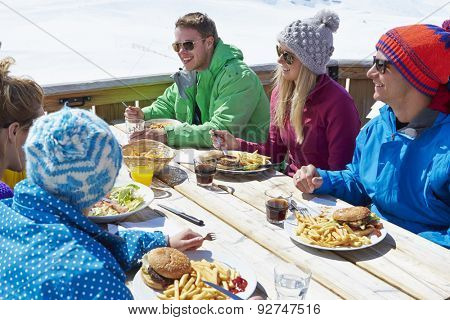 Group Of Friends Enjoying Meal In Cafe At Ski Resort