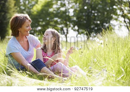 Grandmother And Granddaughter Sitting In Summer Field