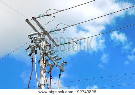 Electric Pole In Front Of A Clouded Blue Sky