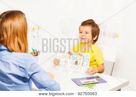 Happy boy holding the drawing with colored shapes