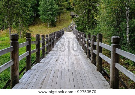 Long Wooden Footbridge In Forest