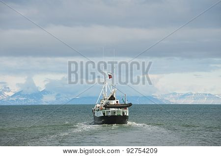 Ship sails from the harbor of Longyearbyen in Longyearbyen, Norway.