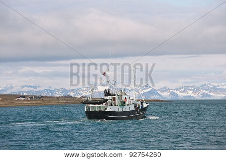Ship sails along the shore of Longyearbyen in Longyearbyen, Norway.