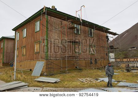 People repair building in the abandoned Russian arctic settlement Pyramiden, Norway.