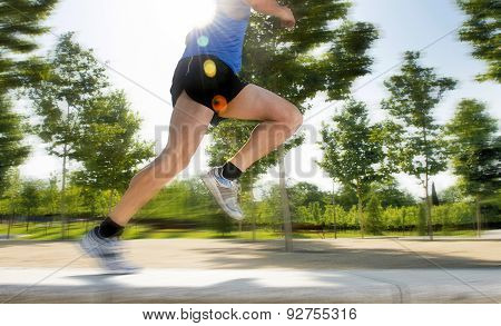 Close Up Athletic Legs Of Young Man Running In City Park On Summer Training In Healthy Lifestyle Con