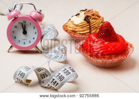 Sweet Food Measuring Tape And Clock On Table
