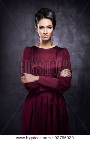 Young and beautiful fashion model posing in a red dress