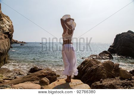 Lady In Hat And White Lace Dress On Rocky Beach.
