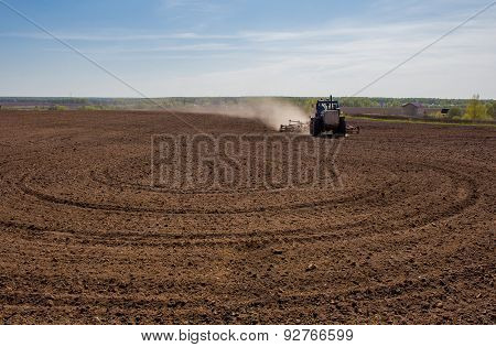 Blue Tractor Plowing A Field Before Planting