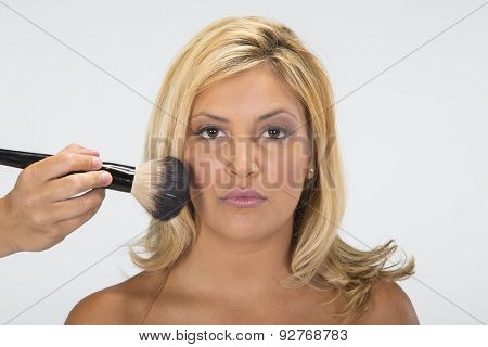 A pretty ethnic blonde model having makeup applied in a studio environment.
