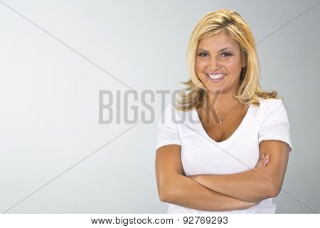 A pretty ethnic blonde model posing in a studio environment.