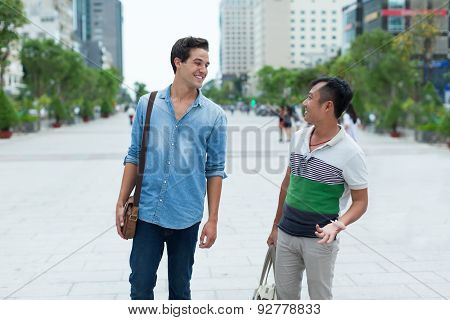 Two men smile talking outdoor, asian mix race friends