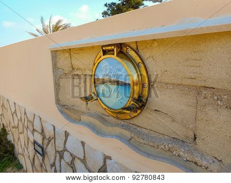 Stone Fence Of The Villa Is Decorated With The Ship's Porthole. Favignana