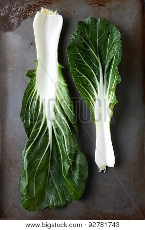 Two bok choy leaves on a used metal baking sheet. Vertical format still life..