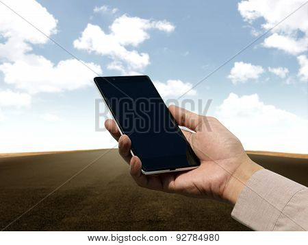 Hand Holding Cellphone With Blank Screen On Empty Road Backgroun