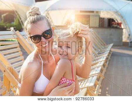 Happy Blond Mother Brushing Long Hair Of Her Daughter Near The Pool