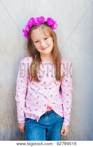 Outdoor portrait of adorable little girl wearing pink floral headband