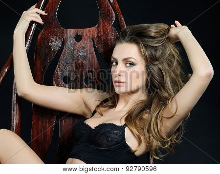 Feminine Sensitive Emotional Woman In Lace Underwear On Wood Chair In The Studio