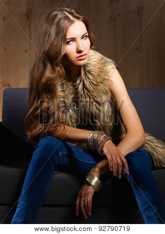 Portrait of a elegant woman sitting on a black sofa wearing a blue jeans and fur vest.