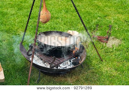 Cooking Soup Over Burning Campfire