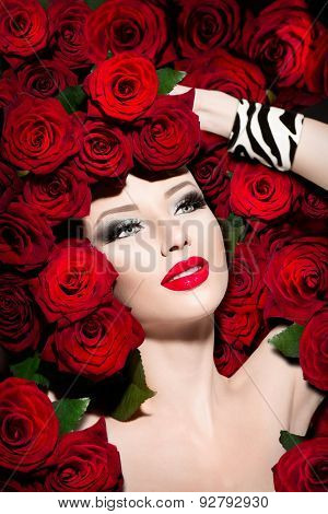Beauty Sexy Fashion Model Girl. High Fashion Vogue style model portrait with red roses flowers hairstyle. Art glamour Woman with bright red make-up and accessories. Holiday makeup