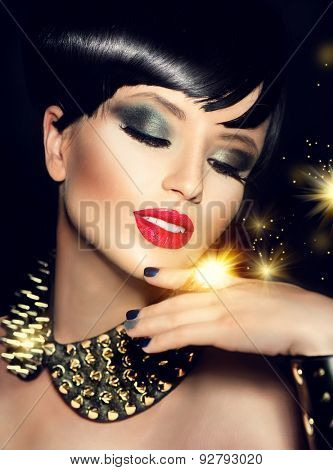 Beauty Fashion Model Girl with bright Makeup and golden Accessories. Rocker Style Brunette Portrait. Short haircut. Fringe Hairstyle. Rocker or Punk sexy Woman. Isolated on black background. Hair cut