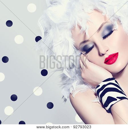 Beauty Fashion Model Girl with White Feathers Hair style and bright make up. Beautiful woman with feathers on her head. Hairstyle. Holiday Creative Makeup and manicure. Polka dots background